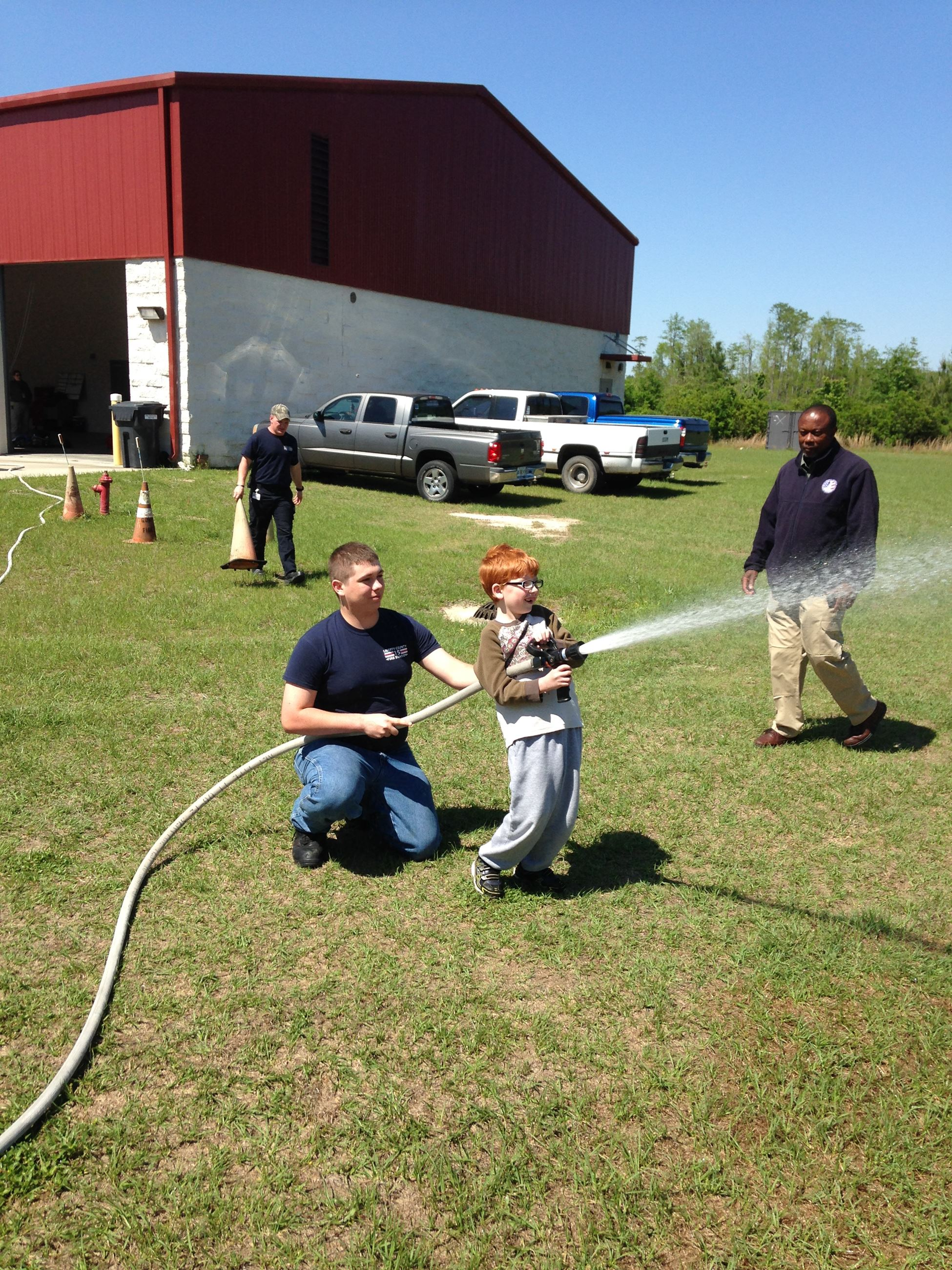 Young Boy Using Fire Hose Supervised by Fire Staff